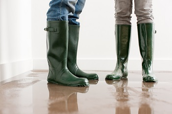 2 people wearing rubber rain boots on wet floor